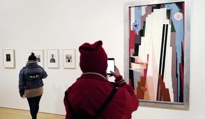 """In this March 16, 2017 photo, a visitor to the Brooklyn Museum in New York photographs the 1932 painting """"Manhattan"""" by American artist Georgia O'Keeffe. The exhibit, """"Georgia O'Keeffe: Living Modern"""" highlights her role as a style icon. (AP Photo/Mark Lennihan)"""