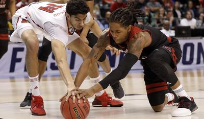 Louisville's Anas Mahmoud, left, and Jacksonville State's Greg Tucker dive after a loose ball during the first half of a first-round game in the men's NCAA college basketball tournament Friday, March 17, 2017, in Indianapolis, Mo. (AP Photo/Jeff Roberson)