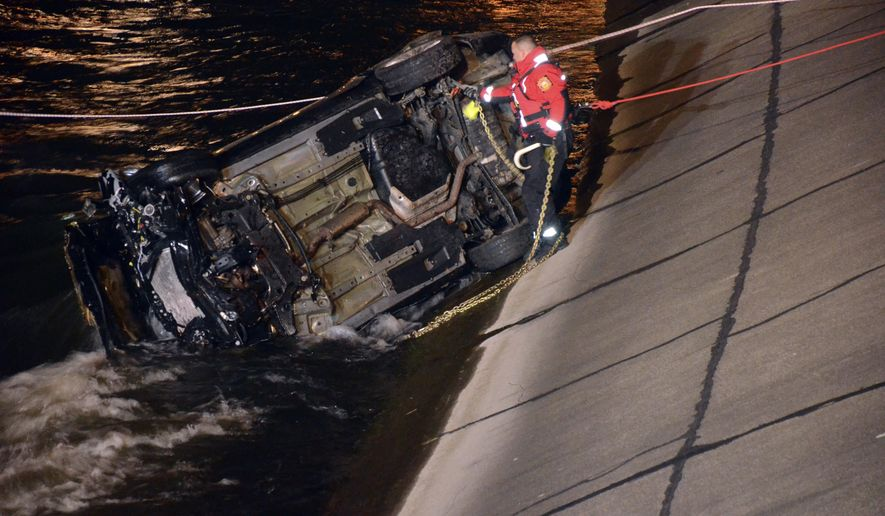 Crews work to remove a vehicle from the Kalamazoo River in Battle Creek, Mich., following a crash on Friday, March 17, 2017. The bodies of two people were found in the vehicle after it was pulled from the water, Battle Creek police said. (Trace Christenson /Battle Creek Enquirer via AP)