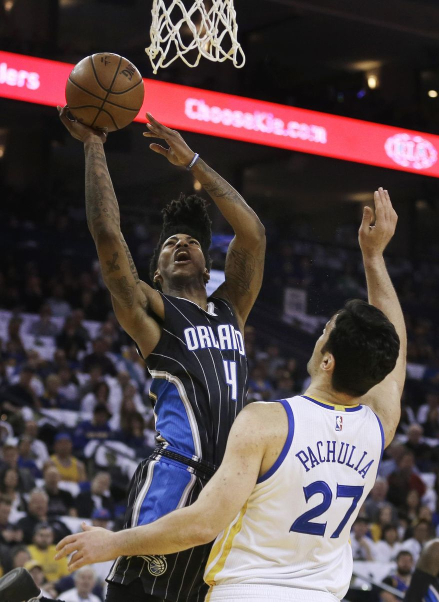 Orlando Magic's Elfrid Payton, left, shoots over Golden State Warriors' Zaza Pachulia during the first half of an NBA basketball game Thursday, March 16, 2017, in Oakland, Calif. (AP Photo/Ben Margot)