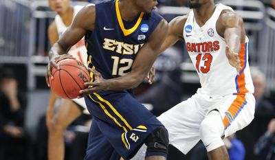 East Tennessee State forward Hanner Mosquera-Perea (12) looks for an open teammate past Florida forward Kevarrius Hayes (13) during the second half of the first round of the NCAA college basketball tournament, Thursday, March 16, 2017 in Orlando, Fla. (AP Photo/Wilfredo Lee)