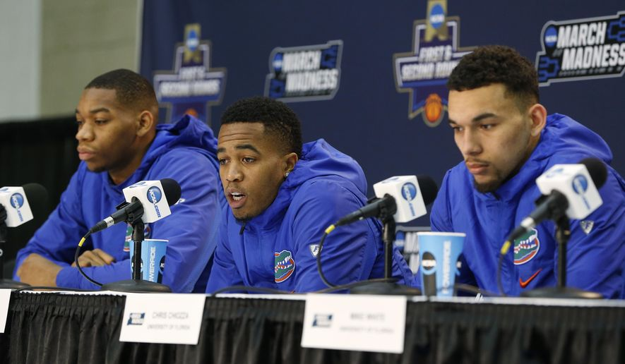 Florida guard Kasey Hill, center, answers a question as he, forward Justin Leon, left, and guard Chris Chiozza speak during a news conference, Friday, March 17, 2017 in Orlando, Fla. Florida will play Virginia in the second round of the NCAA college basketball tournament Saturday in Orlando. (AP Photo/Wilfredo Lee)