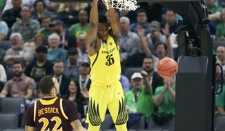 Oregon forward Kavell Bigby-Williams hangs on the rim after dunking as Iona forward Taylor Bessick, left, looks on during the first half of a first-round game in the men's NCAA college basketball tournament in Sacramento, Calif., Friday, March 17, 2017. (AP Photo/Steve Yeater)