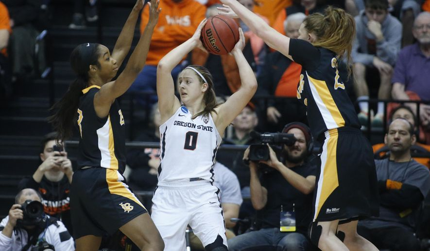 Oregon State's Mikayla Pivec (0) gets double teamed by Long Beach State's Chanterria Jackson, left, and Madison Montgomery, right, during the first half of a first-round game in the women's NCAA college basketball tournament Friday, March 17, 2017, in Corvallis, Ore. (AP Photo/ Timothy J. Gonzalez)