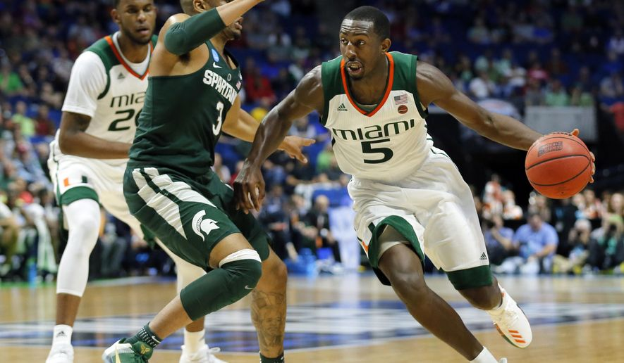 Michigan State guard Alvin Ellis III (3) defends as Miami guard Davon Reed (5) moves to the basket in the first half of a first-round game in the men's NCAA college basketball tournament in Tulsa, Okla., Friday March 17, 2017. (AP Photo/Tony Gutierrez)