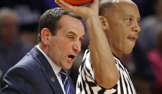 Duke head coach Mike Krzyzewski, left, argues a call with an official during the second half against Troy in a first-round game of the NCAA men's college basketball tournament in Greenville, S.C., Friday, March 17, 2017. (AP Photo/Chuck Burton)