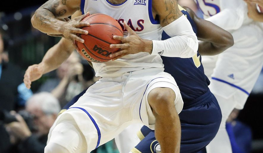 Kansas's Frank Mason III, front, spins UC Davis defenders to get to the basket in the first half of a first-round game in the men's NCAA college basketball tournament in Tulsa, Okla., Friday March 17, 2017. (AP Photo/Tony Gutierrez)