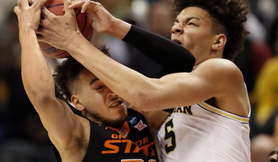 Oklahoma State's Jeffrey Carroll, left, and Michigan's D.J. Wilson reach for a rebound during the first half of a first-round game in the men's NCAA college basketball tournament Friday, March 17, 2017, in Indianapolis, Mo. (AP Photo/Jeff Roberson)