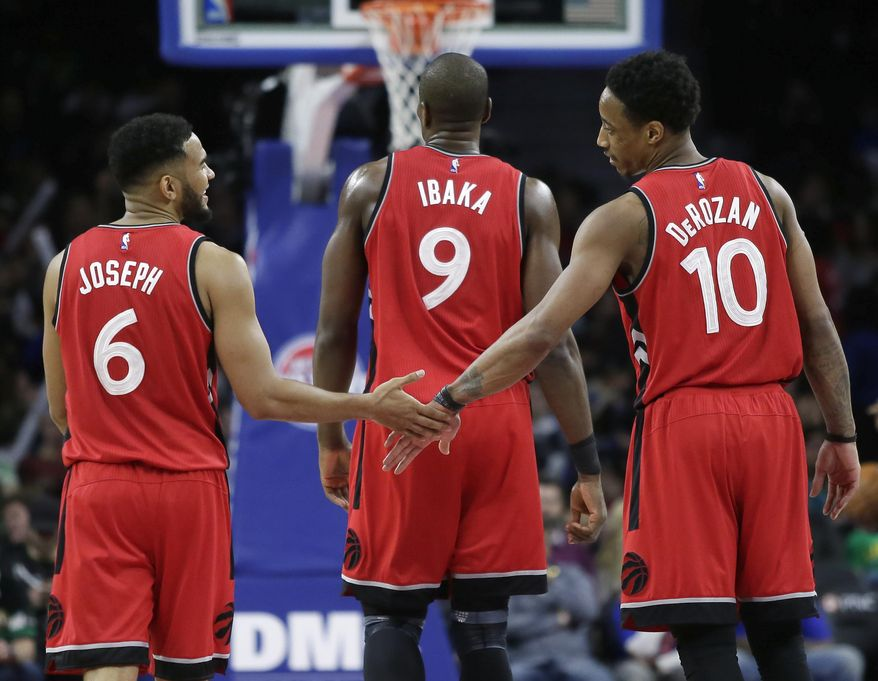 Toronto Raptors guards Cory Joseph (6) and DeMar DeRozan (10) celebrate as they walk downcourt with forward Serge Ibaka (9) during the final seconds of a win over the Detroit Pistons in an NBA basketball game Friday, March 17, 2017, in Auburn Hills, Mich. (AP Photo/Duane Burleson)