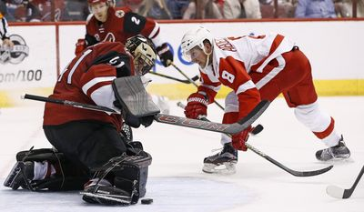 Arizona Coyotes goalie Mike Smith, left, makes a save on a shot by Detroit Red Wings left wing Justin Abdelkader (8) during the second period of an NHL hockey game Thursday, March 16, 2017, in Glendale, Ariz. (AP Photo/Ross D. Franklin)