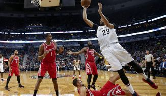 New Orleans Pelicans forward Anthony Davis (23) goes to the basket as Houston Rockets forward Ryan Anderson falls to the court during the first half of an NBA basketball game in New Orleans, Friday, March 17, 2017. (AP Photo/Gerald Herbert)