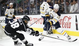 Buffalo Sabres' Jake McCabe, right, passes the puck as Los Angeles Kings' Jarome Iginla defends during the second period of an NHL hockey game Thursday, March 16, 2017, in Los Angeles. (AP Photo/Jae C. Hong)