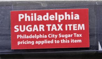 This March 16, 2017, photo shows a sticker alerting customers of the sugar tax posted by sweetened beverages at the IGA supermarket in the Port Richmond neighborhood of Philadelphia. (Associated Press) **FILE**