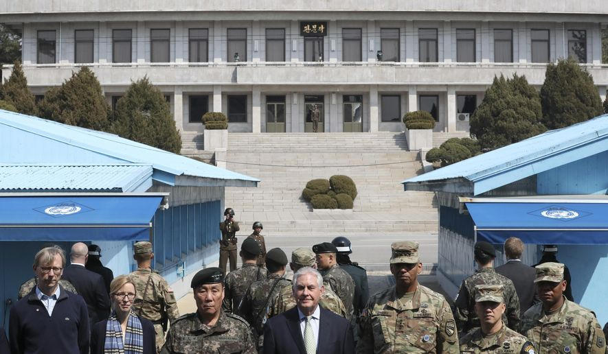U.S. Secretary of State Rex Tillerson, center, stands with U.S. Gen. Vincent K. Brooks, third right, commander of the United Nations Command, Combined Forces Command and United States Forces Korea, and South Korean Deputy Commander of the Combined Force Command Gen. Leem Ho-young, third left, as North Korean soldiers look at the south side at the border village of Panmunjom, which has separated the two Koreas since the Korean War, South Korea, Friday, March 17, 2017. (AP Photo/Lee Jin-man, Pool)