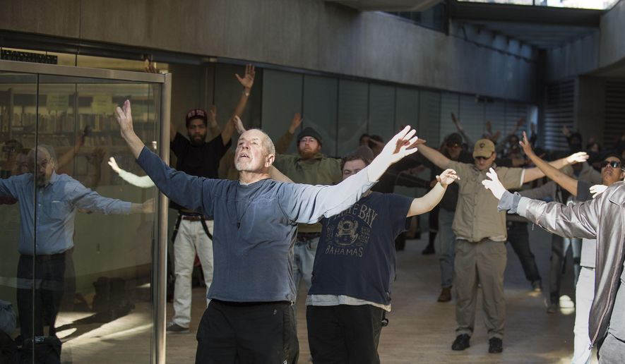 In a Thursday, March 2, 2017 photo, Bernie Hart leads a group of homeless people in tai chi at the Salt Lake City Public Library.  Hart hopes that the slow-paced practice of balance and movement will help these individuals find stability in their lives. The activist started the informal program with his wife, Marita, in September. (Lennie Mahler/The Salt Lake Tribune via AP)