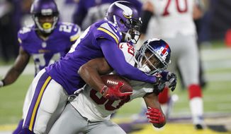 FILE - In this Oct. 3, 2016, file photo, Minnesota Vikings cornerback Terence Newman, left, tackles New York Giants wide receiver Victor Cruz during the first half of an NFL football game, in Minneapolis. Newman wasn't ready to be done with the NFL. The Vikings were more than willing to bring him back for a 15th season at age 39. (AP Photo/Andy Clayton-King, File)