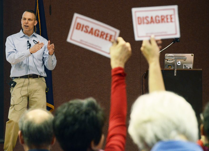 """Audience members hold signs reading, """"DISAGREE"""" as U.S. Rep. Scott Perry, R-Pa., speaks during a town hall meeting Saturday, March 18, 2017 in Red Lion, Pa. Perry's event turned contentious in his conservative south-central Pennsylvania district over questions about his support for President Donald Trump's budget proposal and immigration plans and for undoing former President Barack Obama's signature health care law. (AP Photo/Marc Levy)"""