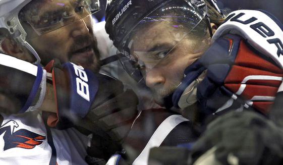 Washington Capitals left wing Alex Ovechkin, left, grabs Tampa Bay Lightning defenseman Victor Hedman as they scuffle in the corner during the first period of an NHL hockey game Saturday, March 18, 2017, in Tampa, Fla. (AP Photo/Chris O'Meara)