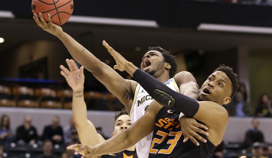 Michigan guard Derrick Walton Jr. (10) is fouled as he shoots by Oklahoma State forward Leyton Hammonds (23) during a first-round game in the men's NCAA college basketball tournament in Indianapolis, Friday, March 17, 2017. (AP Photo/Michael Conroy)