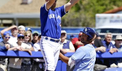 Toronto Blue Jays infielder Jake Elmore signals to hold up the throw as Tampa Bay Rays' Patrick Leonard slides into third base for a triple in the fifth inning of a spring training baseball game, Saturday, March 18, 2017, in Dunedin, Fla. (AP Photo/John Raoux)