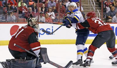 St. Louis Blues left wing Jaden Schwartz, middle, tries to hit the puck in the air as Alex Goligoski, right, defends and goalie Mike Smith, left, moves over to make a possible save during the second period of an NHL hockey game Saturday, March 18, 2017, in Glendale, Ariz. (AP Photo/Ross D. Franklin)
