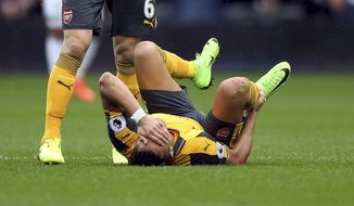 Arsenal's Alexis Sanchez holds his right ankle after sustaining an injury, during the English Premier League soccer match between West Bromwich Albion and Arsenal,  at The Hawthorns, in West Bromwich, England, Saturday March 18, 2017.  (Nick Potts/PA via AP)