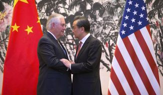 U.S. Secretary of State Rex Tillerson, left, and Chinese Foreign Minister Wang Yi stare each other as they shake hands at the end of a joint press conference following their meeting at the Diaoyutai State Guesthouse in Beijing, China, Saturday, March 18, 2017. Tillerson arrived in Beijing on Saturday for his first face-to-face talks with Chinese leaders expected to focus on North Korea's nuclear program, trade and South China Sea territorial disputes. (AP Photo/Mark Schiefelbein, Pool)