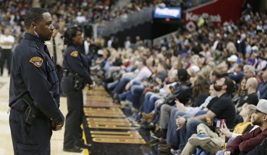 In this Thursday, March 16, 2017, a Cleveland policeman stands watch during an NBA basketball game between the Utah Jazz and the Cleveland Cavaliers, in Cleveland. The city of Cleveland is discussing the creation of a pilot program to test the feasibility of Cleveland police officers wearing body cameras while working part-time jobs in uniform at events like Cleveland Cavaliers home games. The monitoring team overseeing a reform-minded agreement between the city and Justice Department plans to ask a federal judge to require such a policy.(AP Photo/Tony Dejak)