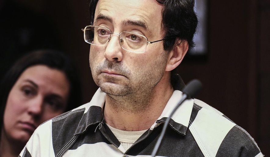 FILE - In this Feb. 17, 2017 file photo, Dr. Larry Nassar listens to testimony of a witness during a preliminary hearing in Lansing, Mich.    Records show a Michigan State University doctor resigned in January after learning the school was considering her termination because she didn't disclose that USA Gymnastics was investigating Dr. Larry Nassar. Nassar is accused of assaulting a girl from the age of 6 until the girl was 12 at his home in Holt, Mich. He has pleaded not guilty. (Robert Killips/Lansing State Journal via AP)