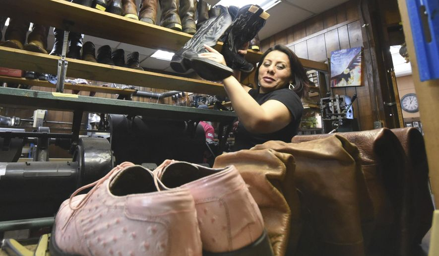Flower Scallia works in the shop at Buddy's Shoe Repair Shop in Hixson, Tenn., on March 10, 2017. Scallia, has survived a recent bout with colon cancer. (Tim Barber/Chattanooga Times Free Press via AP)