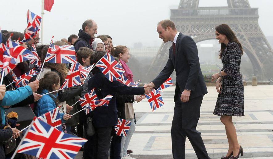Britain's Prince William, the Duke of Cambridge, and his wife Kate, the Duchess of Cambridge, are welcomed by school children and students from the British Council's Somme project as they arrive at the Trocadero square, with the Eiffel Tower in background, in Paris, Saturday, March 18, 2017. (AP Photo/Michel Euler, Pool)