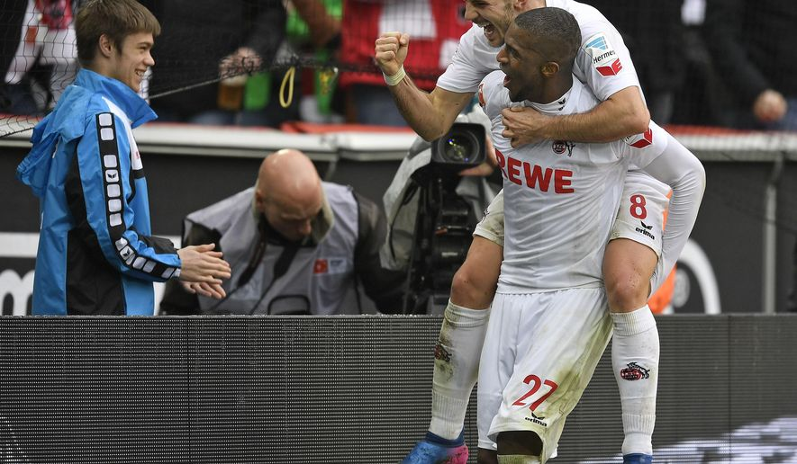 Cologne's Anthony Modeste celebrates his second goal with Cologne's Milos Jojic on his back during the German Bundesliga soccer match between 1.FC Cologne and Hertha BSC Berlin in Cologne, Germany, Saturday, March 18, 2017. (AP Photo/Martin Meissner)