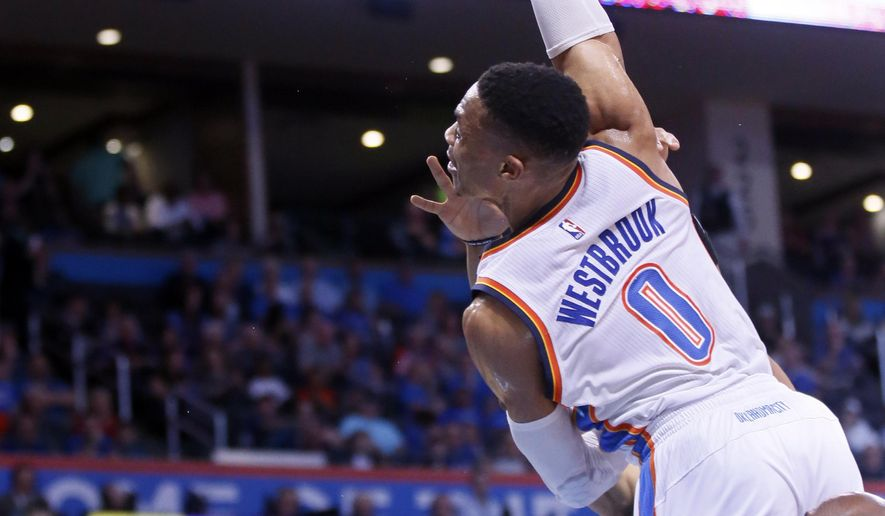 Oklahoma City Thunder guard Russell Westbrook (0) is fouled as he drives between Sacramento Kings forward Skal Labissiere, rear, and forward Anthony Tolliver, right, in the first quarter of an NBA basketball game in Oklahoma City, Saturday, March 18, 2017. (AP Photo/Sue Ogrocki)