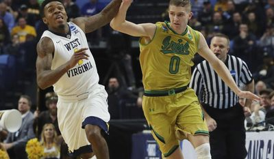West Virginia guard Daxter Miles Jr. (4) and Notre Dame guard Rex Pflueger (0) battle for the ball during the first half of a second-round men's college basketball game in the NCAA Tournament, Saturday, March 18, 2017, in Buffalo, N.Y. (AP Photo/Bill Wippert)
