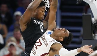 Xavier forward Tyrique Jones (0) blocks a shot by Florida State guard Xavier Rathan-Mayes (22) during the first half of a second-round game in the NCAA men's college basketball tournament, Saturday, March 18, 2017, in Orlando, Fla. (AP Photo/Wilfredo Lee)
