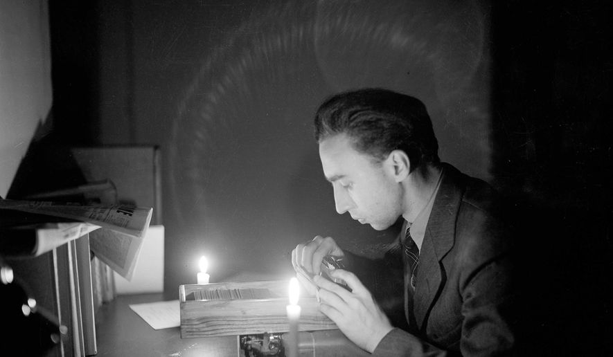 FILE - In this Feb. 1946 file photo, Associated Press correspondent George E. Bria works by candlelight in the AP Rome bureau during a power failure. Bria, the Associated Press newsman who flashed word of the German surrender in Italy at World War II's end has died at age 101. Bria's daughter, Judy Storey, says he died Saturday, March 18, 2017, at a New York hospital after his health had declined for a time. (AP Photo, File)