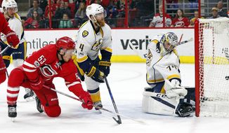 Carolina Hurricanes' Jeff Skinner (53) shoots the puck past Nashville Predators' Ryan Ellis (4) and goalie Juuse Saros (74) for a goal during the second period of an NHL hockey game, Saturday, March 18, 2017, in Raleigh, N.C. (AP Photo/Karl B DeBlaker)