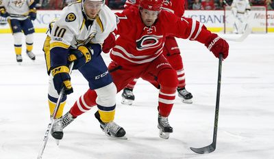 Nashville Predators' Colton Sissons (10) reaches for the puck as Carolina Hurricanes' Ryan Murphy (7) defends during the first period of an NHL hockey game, Saturday, March 18, 2017, in Raleigh, N.C. (AP Photo/Karl B DeBlaker)