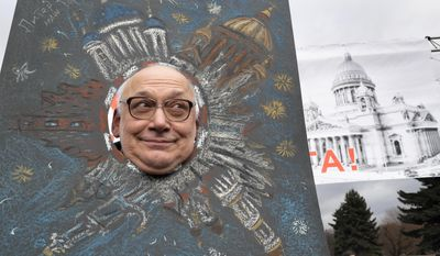 A man looks through a cardboard cutout poster during a protest rally against the decision of the city authorities to hand over the city's landmark St. Isaac's Cathedral to the Russian Orthodox Church in St. Petersburg, Russia, Saturday, March 18, 2017. About four thousand people gathered for a protest against the controversial return of the renowned cathedral to the Russian Orthodox Church. (AP Photo/Dmitri Lovetsky)
