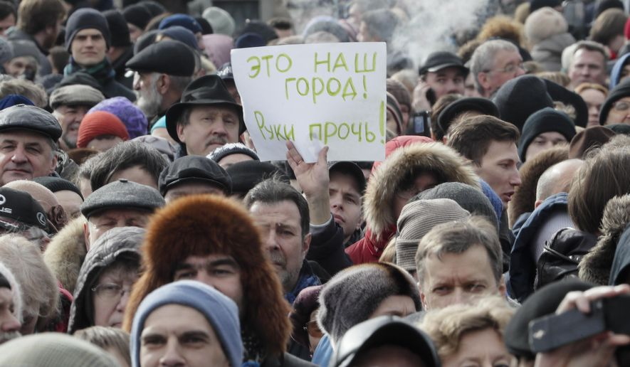People rally to protest against the decision of the city authorities to hand over the city's landmark St. Isaac's Cathedral to the Russian Orthodox Church in St.Petersburg, Russia, Saturday, March 18, 2017. About four thousand people gathered for a protest against the controversial return of the renowned cathedral to the Russian Orthodox Church. The poster reads: 'This is our city. Hands off!'. (AP Photo/Dmitri Lovetsky)