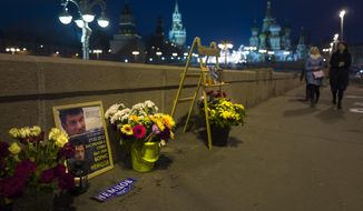 In this Thursday, March 16, 2017 photo, people walk past portraits and flowers at the place where Russian opposition leader Boris Nemtsov was gunned down a two years ago, in Moscow, with St. Basil Cathedral in the background in Moscow, Russia.  (AP Photo/Alexander Zemlianichenko)