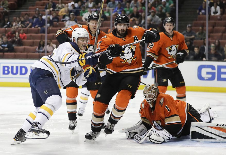 Buffalo Sabres' Jack Eichel, left, and Anaheim Ducks' Ryan Kesler chase the puck deflected by Ducks goalie Jonathan Bernier during the first period of an NHL hockey game Friday, March 17, 2017, in Anaheim, Calif. (AP Photo/Jae C. Hong)