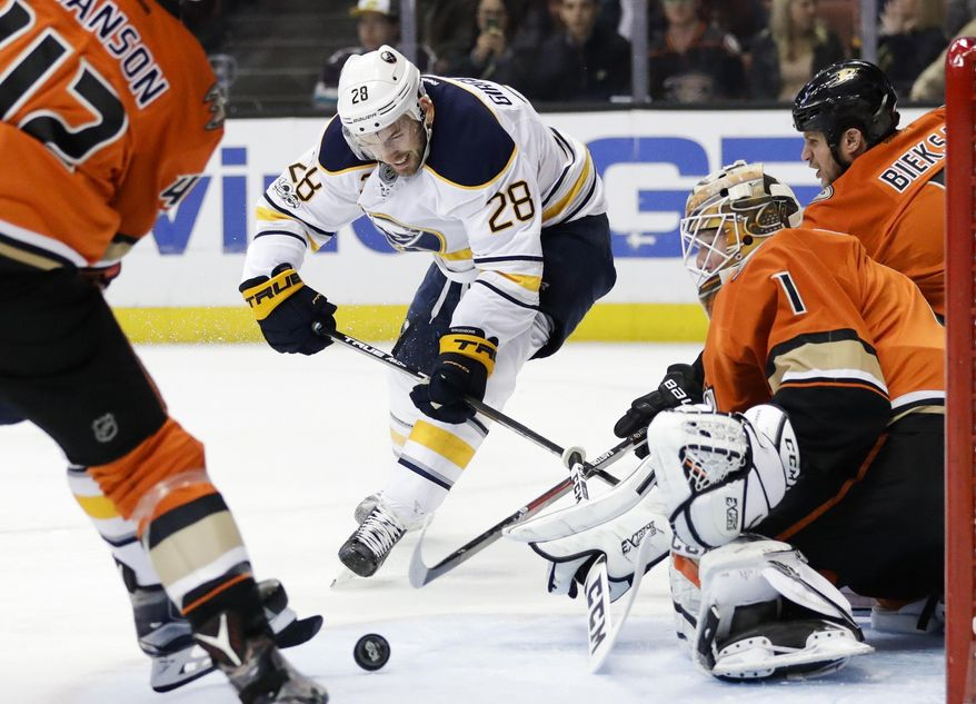 Anaheim Ducks goalie Jonathan Bernier, right, deflects the puck hit by Buffalo Sabres' Zemgus Girgensons, center, of Latvia, during the first period of an NHL hockey game Friday, March 17, 2017, in Anaheim, Calif. (AP Photo/Jae C. Hong)