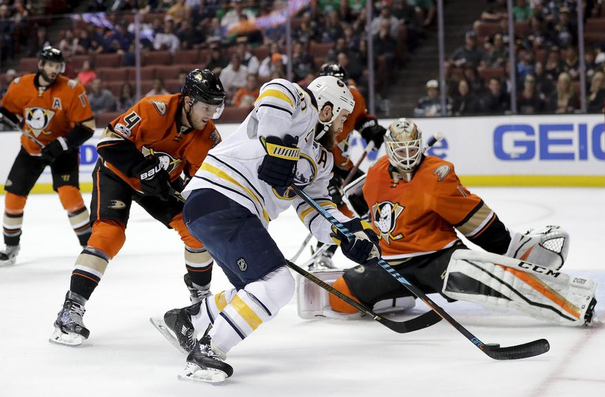 Buffalo Sabres' Ryan O'Reilly, center, moves the puck toward Anaheim Ducks goalie Jonathan Bernier past Ducks' Cam Fowler, left, during the first period of an NHL hockey game Friday, March 17, 2017, in Anaheim, Calif. (AP Photo/Jae C. Hong)
