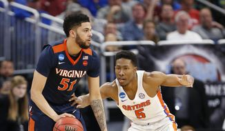 Virginia guard Darius Thompson (51) looks for an open teammate past Florida guard KeVaughn Allen (5) during the first half of the second round of the NCAA college basketball tournament, Saturday, March 18, 2017 in Orlando, Fla. (AP Photo/Wilfredo Lee)