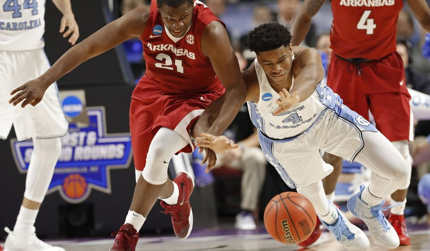 Arkansas' Manuale Watkins (21) and North Carolina's Isaiah Hicks (4) chase a loose ball during the first half in a second-round game of the NCAA men's college basketball tournament in Greenville, S.C., Sunday, March 19, 2017. (AP Photo/Chuck Burton)