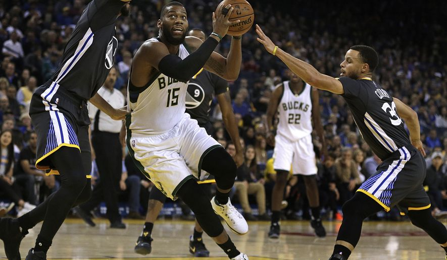 Milwaukee Bucks' Greg Monroe (15) drives the ball between Golden State Warriors' JaVale McGee, left, and Stephen Curry during the first half of an NBA basketball game Saturday, March 18, 2017, in Oakland, Calif. (AP Photo/Ben Margot)