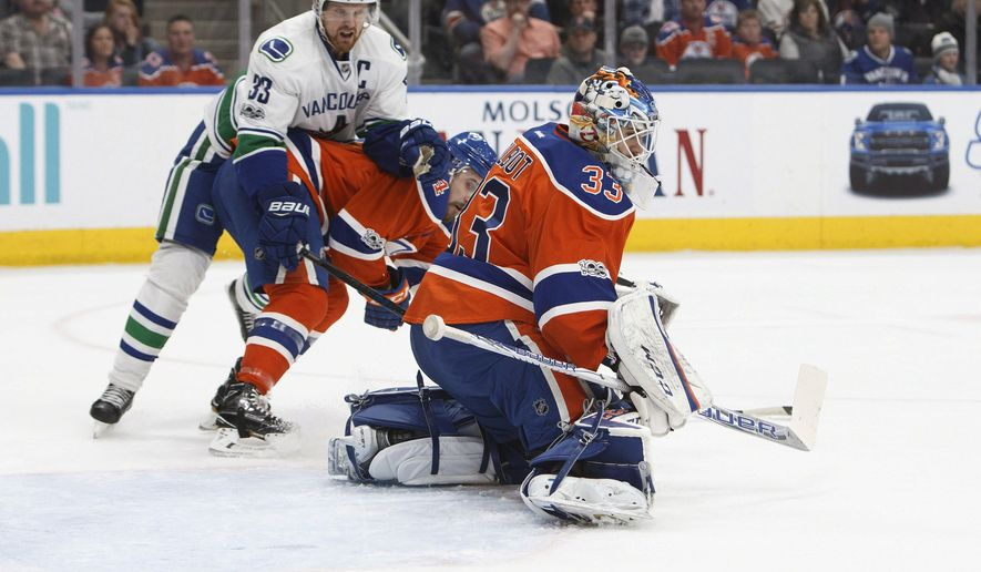 Edmonton Oilers goalie Cam Talbot (33) makes a stop as Vancouver Canucks' Henrik Sedin (33) vies for position in front of the net during the first period of an NHL hockey game Saturday, March 18, 2017, in Edmonton, Alberta. (Codie McLachlan/The Canadian Press via AP)