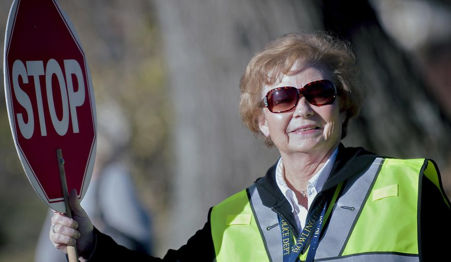ADVANCE FOR WEEKEND EDITIONS - In this Wednesday, March 8, 2017, file photo, Betty Natcher, who has been a crossing guard for 40 years, poses for a photo as she stops traffic for children crossing a street in Bowling Green, Ky. (Bac Totrong/Daily News via AP, File)