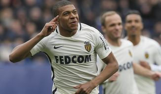 Monaco's Kylian Mbappe celebrates with teammates after he scored the first goal during their French League One soccer match against Caen, in Caen, north western France, Sunday, March 19, 2017. (AP Photo/David Vincent)